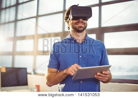 Male business executive in virtual reality headset using digital tablet in office