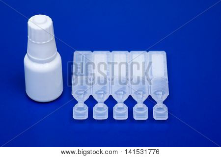 Lubricant eye drops vials and eye drop bottle on blue background