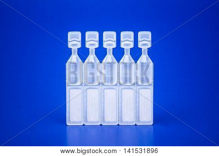 Lubricant eye drops vials on blue background