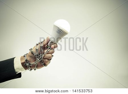 Hand holding a turned on LED light bulb chained and lock / Something stops new idea / Freedom of thought
