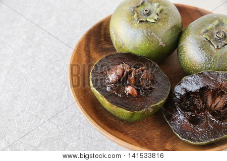 Black sapote chocolate pudding fruit in wooden plate