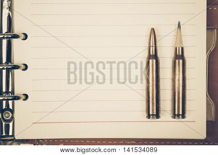 A rifle bullet with a pencil at the head / Using idea as weapon concept