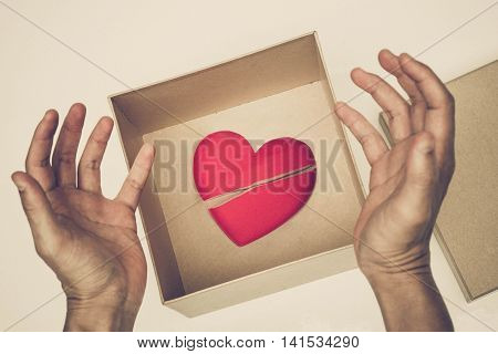 Broken red heart in a paper box / difficult love and obstacle