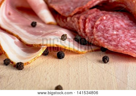 Slices Of Pink Bacon And Salami With Black Peppercorn On Wooden