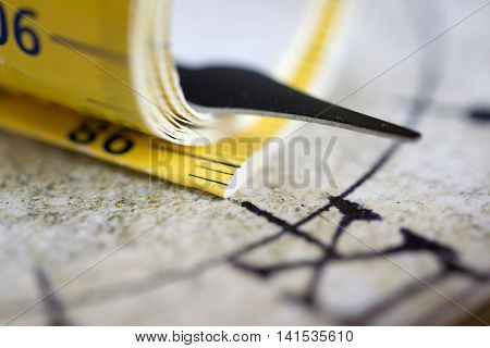 tape-measure wrapped around at a hands of an old clock. Time measure