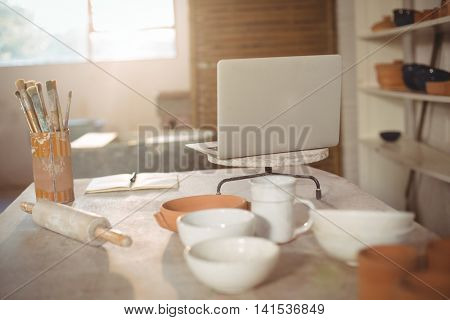 Laptop with earthenware pots and paint brush in pottery workshop