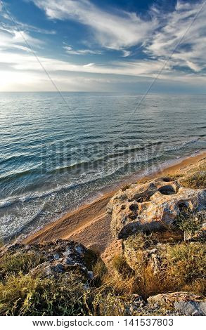 stone rock on a sandy seashore with blue sky
