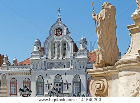 TIMISOARA ROMANIA - AUGUST 5 2016: Orthodox bishop's residence and part from Holy Trinity Statue located on Union Square in Timisoara Romania.