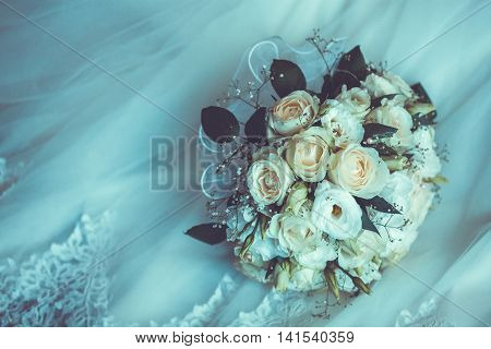 Bridal Boquet on the white wedding dress. close up