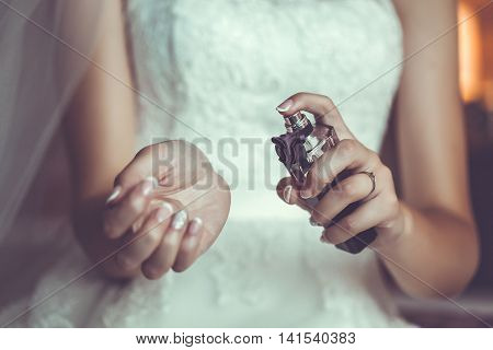 Bride's hands holding a bottle with parfumes. Close up