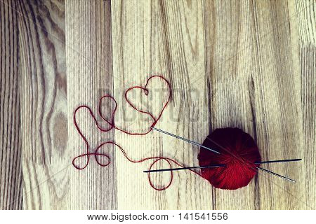 Knitting hobby concept. Red wool ball and heart shaped thread on wooden background. Toned image