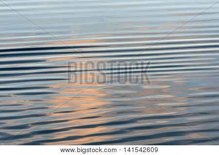Abstract natural background with reflections of sky and clouds and a beautiful soft waves on the blue water of the lake at sunset