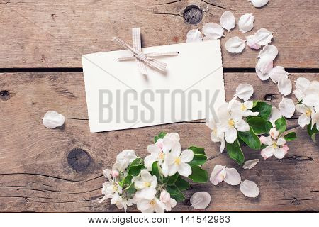 Empty tag and tender apple tree flowers on aged vintage wooden background. Selective focus is on tag. Place for text. Toned image.