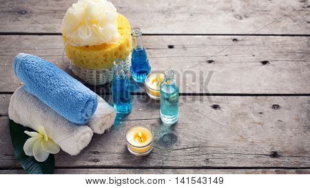 Spa or wellness setting in blue yellow and white colors. Bottles wih essential aroma oil towels candles and wispes on wooden background. Selective focus. Place for text. Toned image.