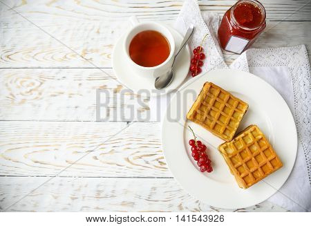 Waffles with red currant jam and berries on a white plate and tea on the wooden background
