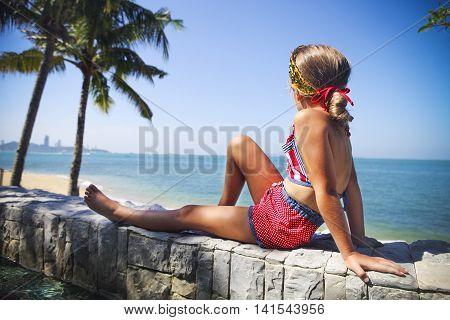 Cute little girl sitting underneath a palm at the tropical beach