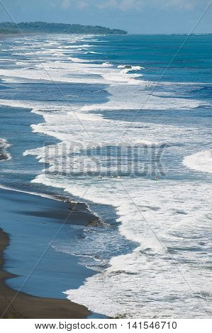 JACO, COSTA RICA - JUNE 23, 2012: Unidentified people bathe at he black volcanic lava beach in the Pacific ocean in Jaco, Costa Rica.
