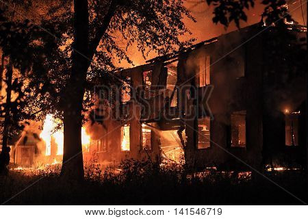 burning house in the darkness. The house almost destroed.