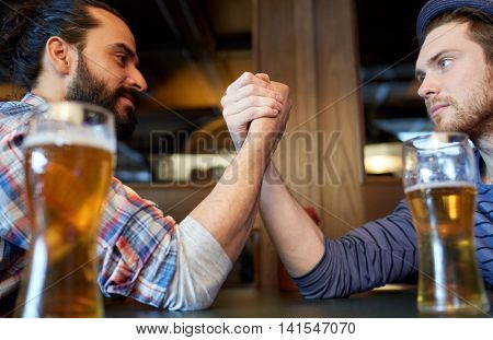 people, leisure, challenge, competition and rivalry concept - male friends arm wrestling and drinking draft beer at bar or pub