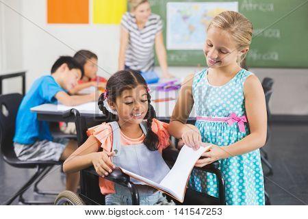 School kids reading book in classroom at school