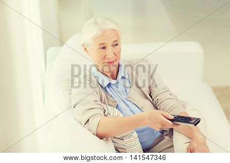 technology, television, age and people concept - senior woman watching tv and changing channel with remote control at home