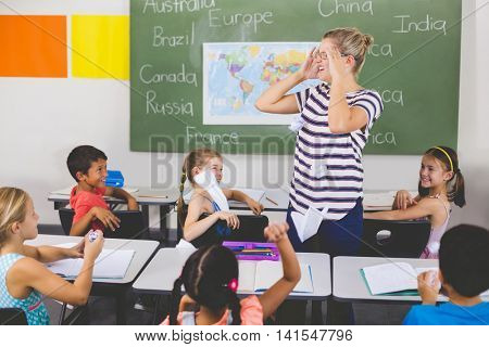 School kids throwing paper balls on teacher in classroom at school