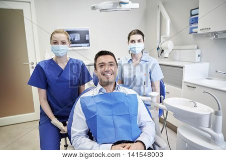 people, medicine, stomatology and health care concept - happy female dentists with man patient at dental clinic office