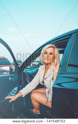 Tanned middle aged woman sitting inside the car keeps auto door on parking. Right to drive Documents exam modern life concept. Roadtrip travel vacation theme.