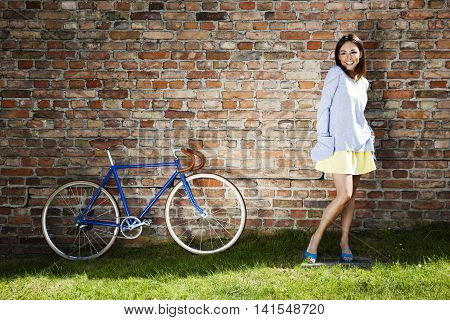 Young Cheerful Woman And Old Blue Bike