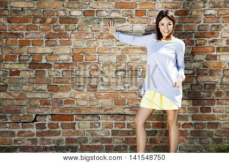 Cheerful Girl Against A Brick Wall
