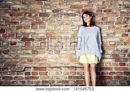 Pensive Woman Against A Brick Wall