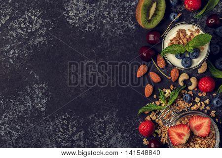 Tasty ingredients (granola fruits berries yogurt and nuts) for breakfast top view. Healthy food Diet Detox Clean Eating or Vegetarian concept.
