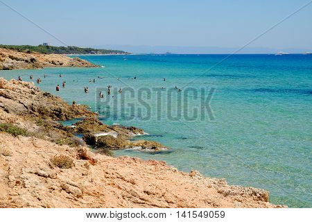 View on the beach with persons swimming in the emerald sea water in Pinus Village in Sardinia Italy.