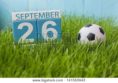 September 26th. Day 26 of month, wooden color calendar on green grass lawn background. Autumn time. Empty space for text.