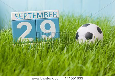 September 29th. Day 29 of month, wooden color calendar on green grass lawn background. Autumn time. Empty space for text.