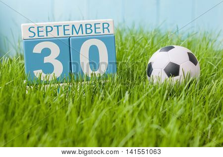 September 30th. Day 30 of month, wooden color calendar on green grass lawn background. Autumn time. Empty space for text.