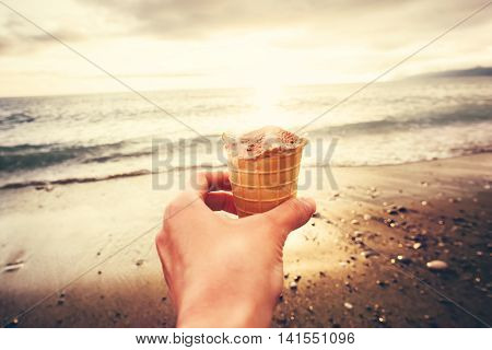 Hand holding Ice Cream with sea beach sunset on background Summer vacations Travel Lifestyle concept