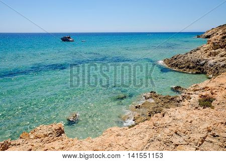 The coast in Pinus Village and a boat in the sea in Sardinia.