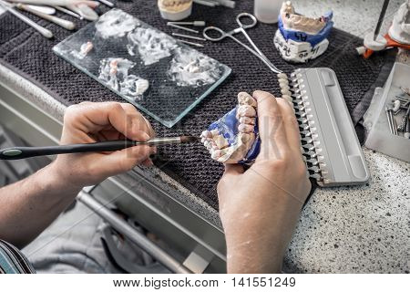 Dental technician working on dentures painting, dental concept