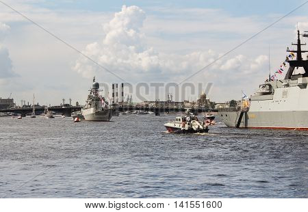St. Petersburg, Russia - 31 July, The boat passes by building ships, 31 July, 2016. Festive parade of warships on the Neva River in St. Petersburg.