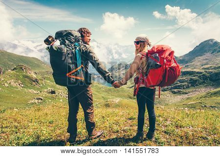 Happy Couple Man and Woman backpackers together holding hands hiking Travel Lifestyle adventure vacations concept mountains and clouds landscape on background