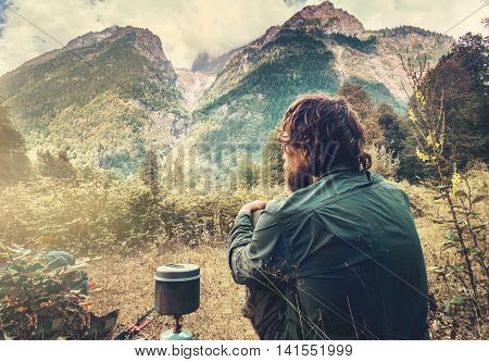 Man Traveler relaxing and cooking with touristic kettle Travel Lifestyle concept mountains landscape on background adventure vacations outdoor