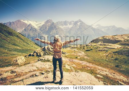 Happy Woman Traveler hands raised hiking with rocky mountains landscape Travel Lifestyle concept adventure summer vacations rear view