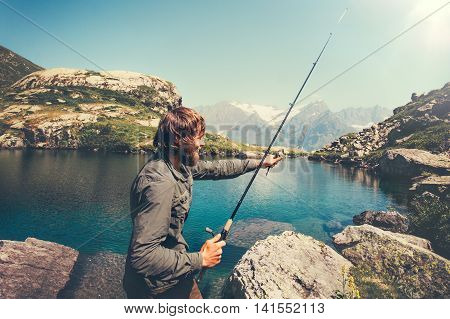 Man Fisherman fishing with rod alone lake and mountains landscape on background Lifestyle Travel survival concept