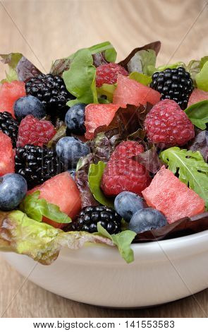 Fruit salad with blackberry raspberry blueberry watermelon slices and mix of green leaves