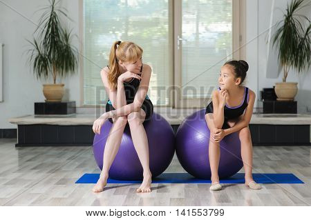 Two girls in the gym. Two pretty sports girls sit on gymnastic balls in gym and looking at each others. Young japanese girl gymnast and young blonde woman smile at each other.