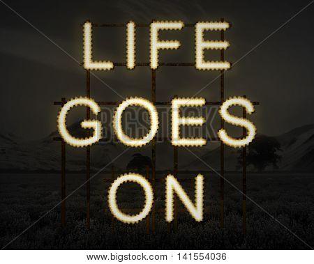 Life Goes On Inspiring Text In Lights Against Dark Landscape Background