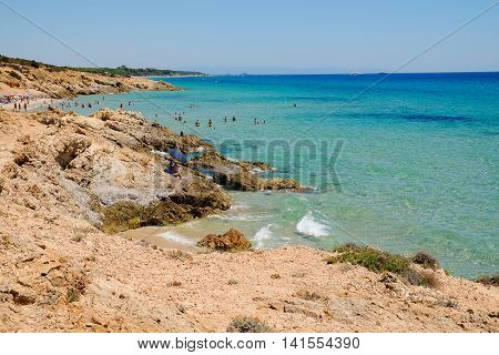 View from above on the rocks and the beach in Pinus Village and swimming unknown persons. 02.08.2016, Sardinia.