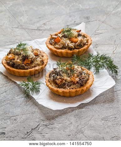 Homemade savory autumn tarts with fresh seasonal mushrooms in a crisp pastry base on gray background