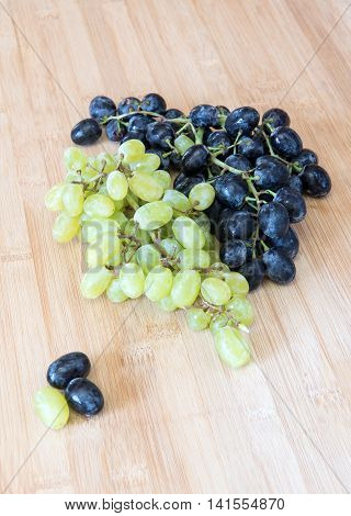 Branch of fresh healthy red and green grapes for wine on a wooden board